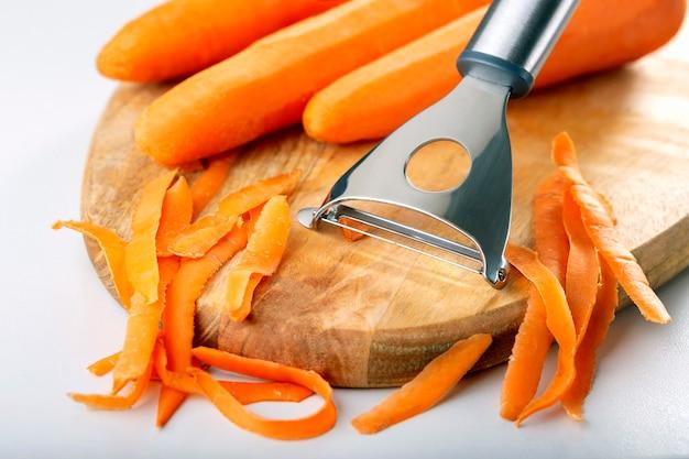 新鮮な野菜にんじん。木製のまな板にニンジンをはがします。コンセプトは健康的な料理を準備します。