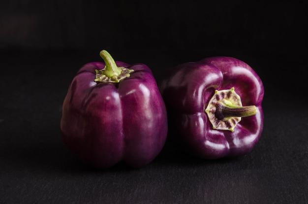 Fresh vegetable. dark purple peppers on black stone