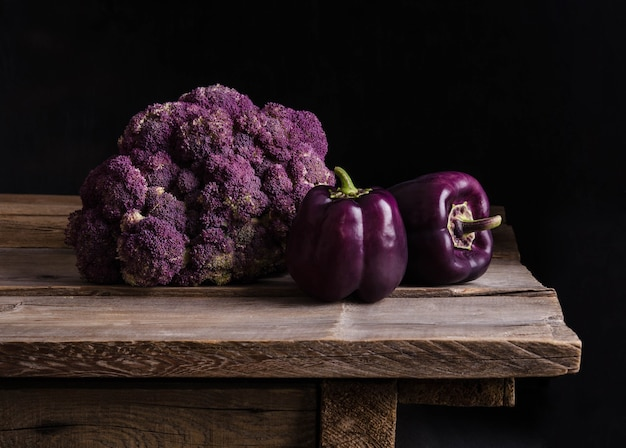 Fresh vegetable. dark purple peppers and cauliflower on old rustic wooden table