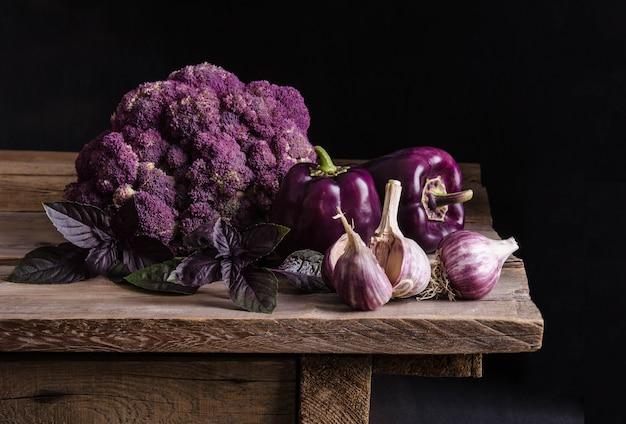Fresh vegetable. dark purple peppers, cauliflower with leaves of basil and garlic