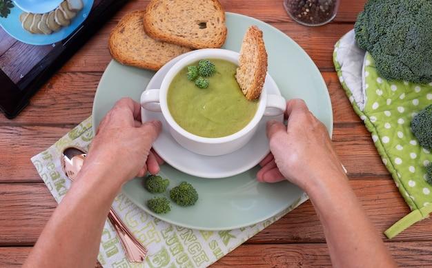 インターネットのレシピに従ってブロッコリーで作った新鮮な野菜のデトックススープ。健康的な栄養の概念。家庭の台所の素朴な木製のテーブル
