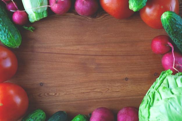 Fresh vegetable frame on wooden background with frame