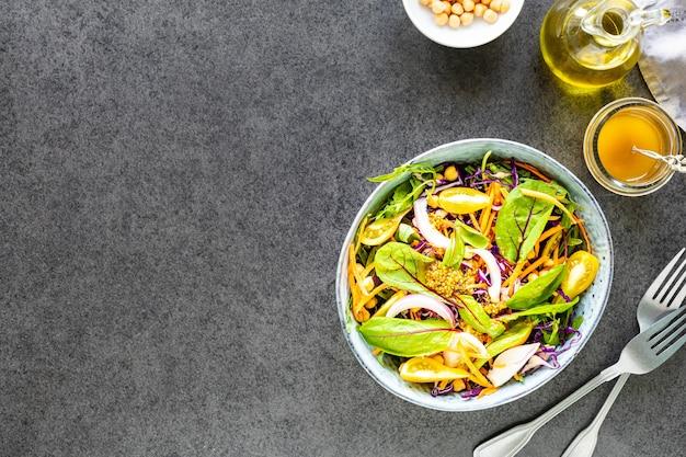 Verdura fresca e insalata di frutta in un piatto su pietra nera. vista dall'alto