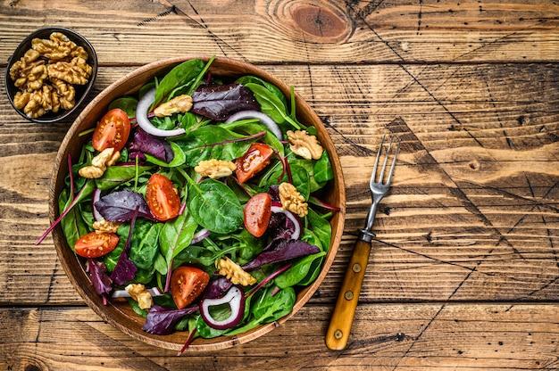 잎 망골드, 스위스 차드, 시금치, 아루굴라, 견과류를 곁들인 신선한 야채 그린 샐러드. 나무 배경입니다. 평면도. 공간을 복사합니다.
