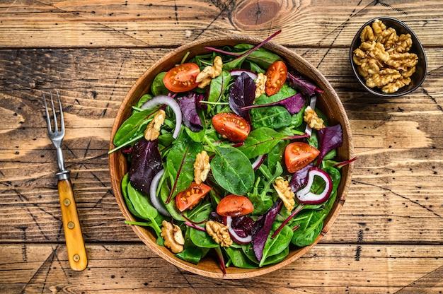 Зеленый салат из свежих овощей с листьями мангольда, мангольдом, шпинатом, рукколой и орехами