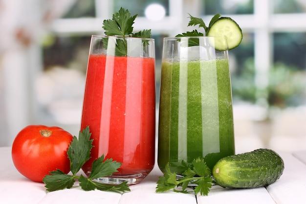 Свежие овощные соки на деревянном столе, на окне