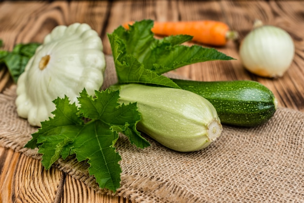 Fresh vegetable marrows, cucumbers, carrots and greens on a wooden background