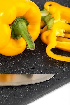 Peperone dolce giallo pieno maturo maturo della verdura fresca sullo scrittorio scuro e sul fondo bianco