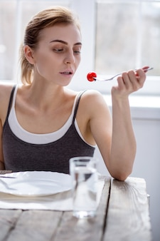 신선한 야채. 아침 식사하는 동안 토마토를보고 슬픈 창백한 여자