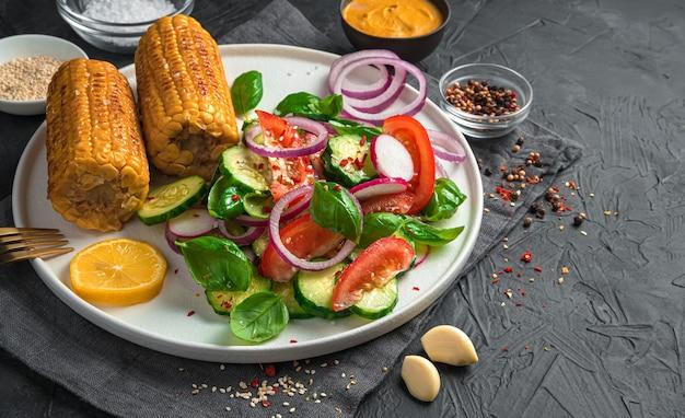 暗い壁に新鮮な野菜のサラダとトウモロコシ、スパイス、ニンニク、ソースが暗い壁に。水平ビュー、コピー スペース。