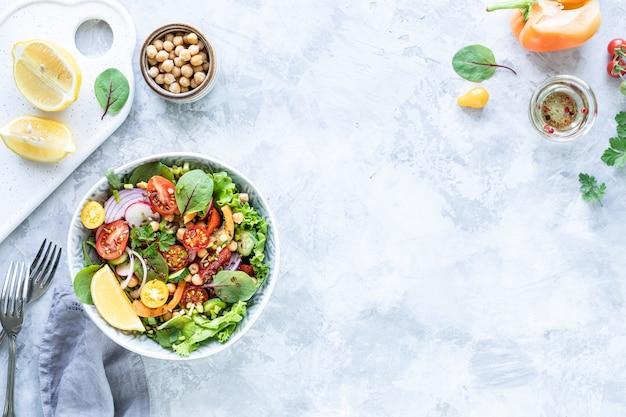 白いコンクリートの表面のプレートに新鮮な野菜のサラダ