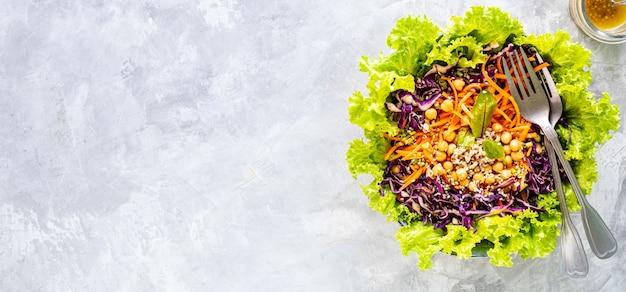 白いテーブルの上の皿に新鮮な野菜サラダ