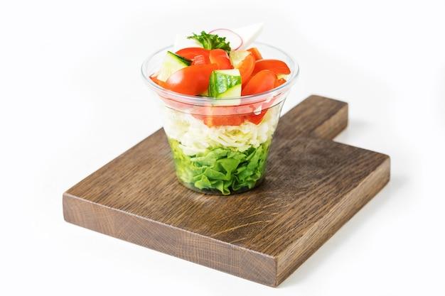 白で隔離のプラスチックの箱の新鮮な野菜サラダ。新鮮なオーガニックミックスグリーンサラダをどうぞ。 fst食品のコンセプト。