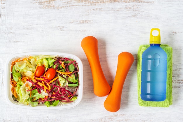Fresh vegetable salad in lunch box with orange dumbbells and energy water drink on white rusty wood