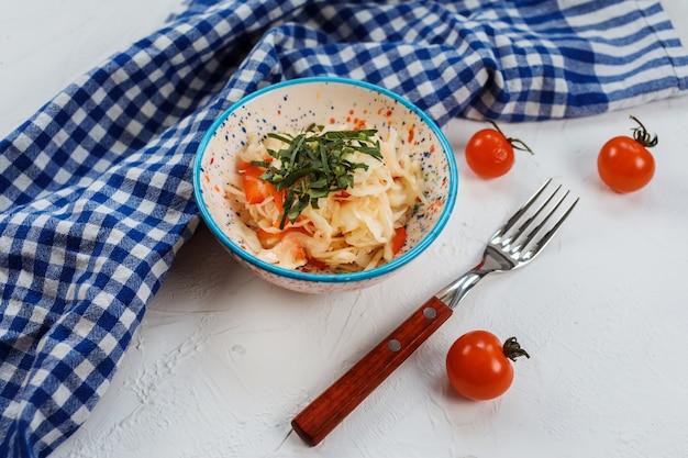 Салат из свежих овощей из капусты и моркови на белом.