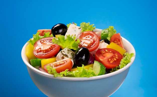Салат из свежих овощей, ингредиенты средиземноморской кухни, греческий салат на синем