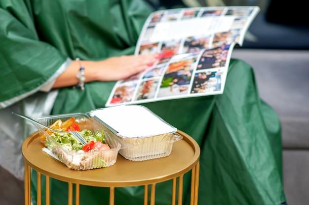 若い女性が美容院で雑誌を読んでいる間、テーブルの上の新鮮な野菜サラダ。