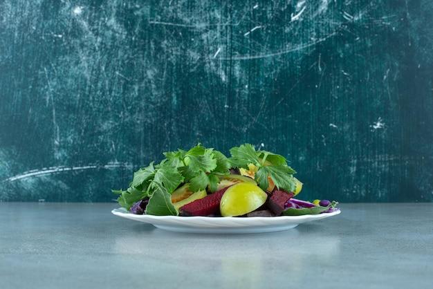 Салат из свежих овощей на белой тарелке.