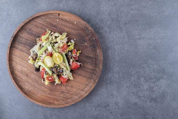 Салат из свежих овощей на деревянной тарелке.