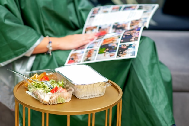 Fresh vegetable salad on the table during young woman reading magazine in beauty salon.