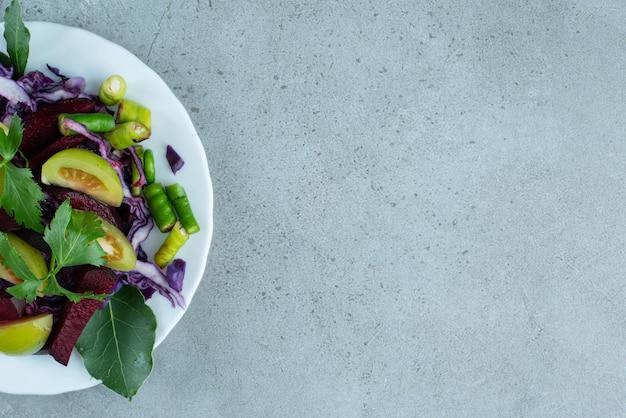 Insalata di verdure fresche sul piatto bianco.
