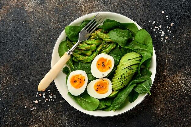 아보카도, 아스파라거스, 어두운 콘크리트 표면에 삶은 계란과 신선한 야채 샐러드. 평면도.