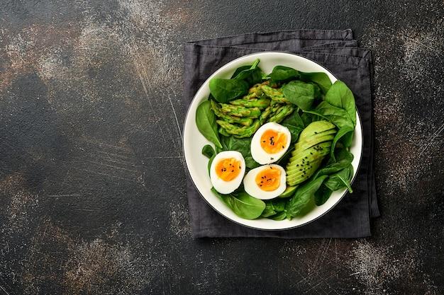 아보카도, 아스파라거스, 구겨진 계란 검은 참깨 시금치를 접시에 넣은 신선한 야채 샐러드