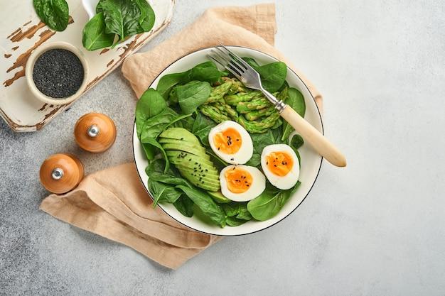 아보카도, 아스파라거스, 검은 참깨가 든 구겨진 계란, 시금치를 밝은 슬레이트, 돌 또는 콘크리트 배경 위에 접시에 얹은 신선한 야채 샐러드. 그릇에 균형 잡힌 점심. 평면도. 조롱.