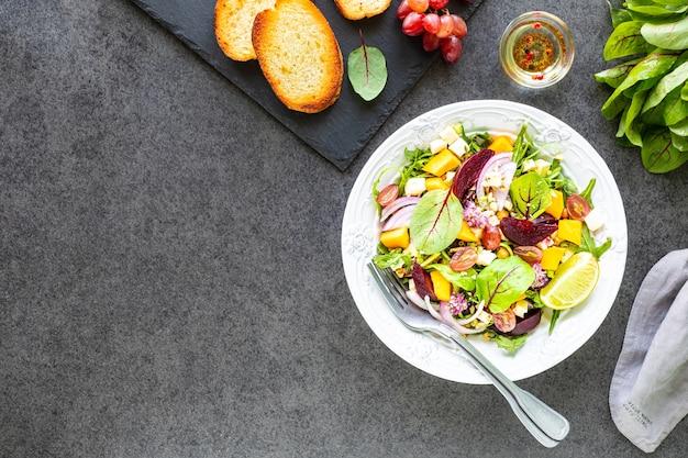 검은 색 표면에 흰색 접시에 사탕 무 우, arugula, 붉은 양파, 밤색, 병아리 콩, 호박, 포도와 신선한 야채 샐러드. 평면도
