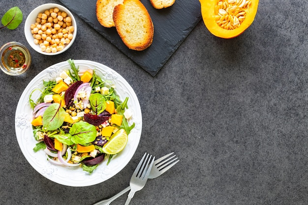 Салат из свежих овощей со свеклой, рукколой, красным луком и щавелем в белой тарелке с тыквой, тостами и нутом