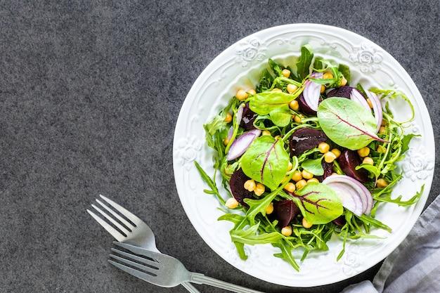 白いプレートにビート、ルッコラ、赤玉ねぎ、スイバの新鮮な野菜サラダ