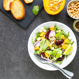 Insalata di verdure fresche con barbabietole, rucola, cipolla rossa e acetosa in un piatto bianco con zucca, toast e ceci