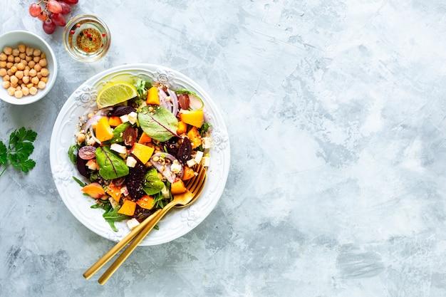 白い石の表面の白いプレートにビート、ルッコラ、赤玉ねぎ、スイバ、ひよこ豆、桃、ブドウの新鮮な野菜サラダ。上面図