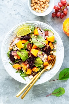 Fresh vegetable salad with beets, arugula, red onions, sorrel, chickpeas, peaches and grapes in a white plate on white stone. top view