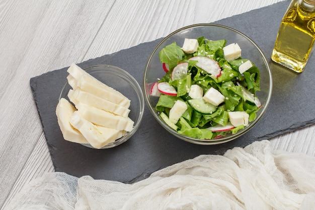 ガラスのボウルにチーズ、キュウリ、大根の新鮮な野菜サラダ。チーズとサラダが入ったガラスのボウル、黒い石のボードにオイルのボトル。上面図。