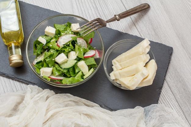 ガラスのボウルにチーズ、キュウリ、大根の新鮮な野菜サラダ。サラダとチーズ、フォーク、黒い石のボード上のオイルのボトルとガラスのボウル。上面図。