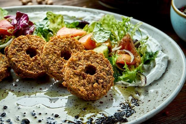 Салат из свежих овощей с фалафелем и оливковым маслом подается в синей тарелке на деревянном фоне. еда в ресторане