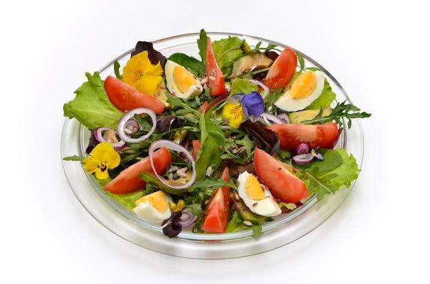 흰색 바탕에 접시에 꽃과 신선한 야채 샐러드
