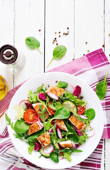 Fresh vegetable salad with grilled chicken breast   - tomatoes, cucumbers, radish and mix lettuce leaves. chicken salad. healthy food.