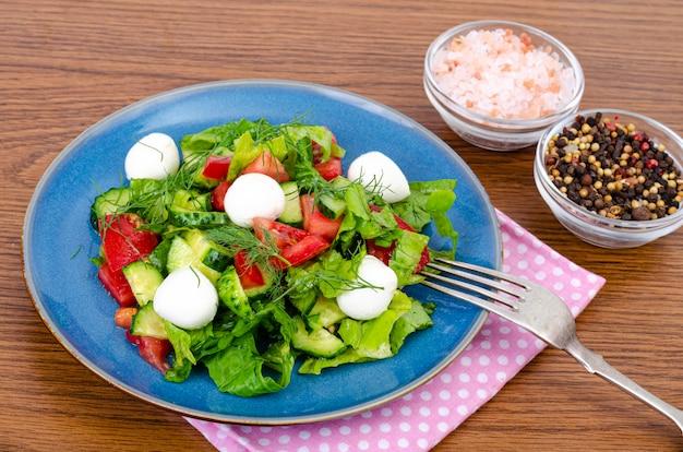 Салат из свежих овощей с шариками из моцареллы. студийное фото