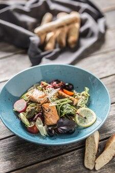 구운 연어 올리브 오일과 바게트를 곁들인 신선한 야채 샐러드.