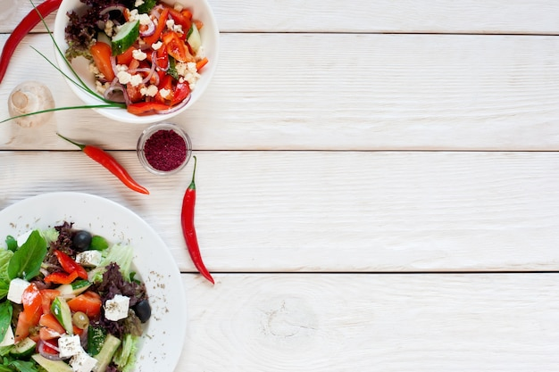 Салаты из свежих овощей на белом деревянном столе плоской планировки. вид сверху на кухонный стол с двумя вегетарианцами
