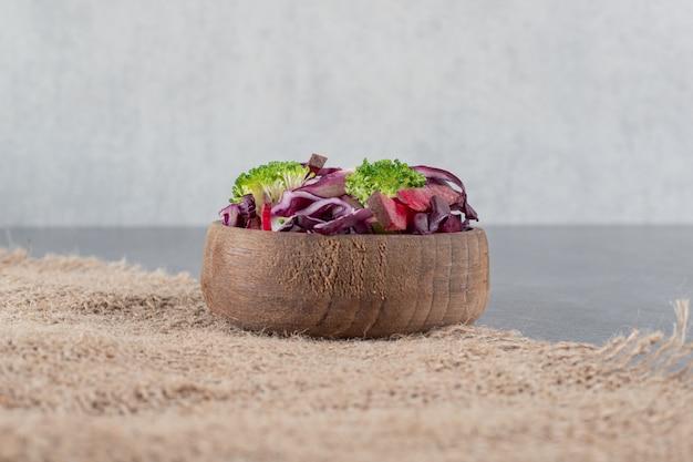 Ломтики свежих овощей в деревянной миске. фото высокого качества