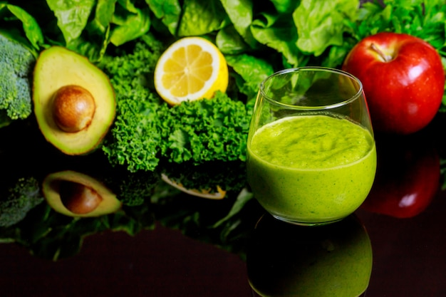 Fresh vegetable smoothie with ingredients on black background.