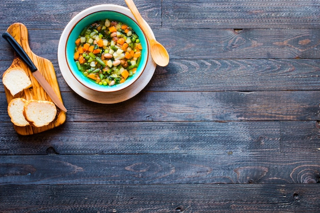 Суп из свежих овощей, приготовленный дома, на деревянном деревенском столе, вид сверху