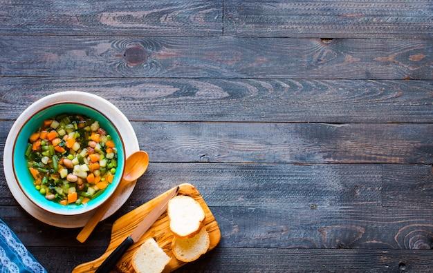 自宅で作られた新鮮な野菜スープ、木製の素朴なテーブル、トップビュー