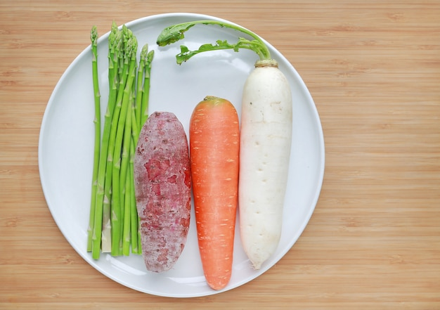 Fresh vegetable on white plate on wood background