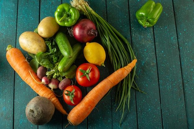 Свежие овощи - вид сверху на спелый салат с витаминами, например, апельсин, морковь, картофель, красные помидоры и другие на зеленой деревенской поверхности.