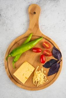 Свежие овощи и сыр на деревянной доске.