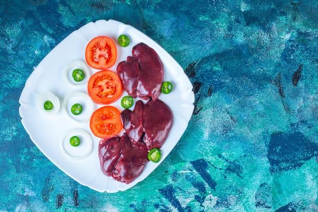 新鮮な野菜と鶏レバーを皿に盛り付けます